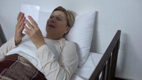 Desperat sjuk kvinnlig som ligger i sjukhussäng och att se familjfotoet och att gråta lager videofilmer