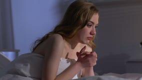 Desperat ung kvinna som sitter i säng på natten, ögon som är fulla av revor, problem stock video