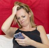 Desperata kvinnablickar som äcklas på skärmen av hennes smartphone som sätter hennes händer i hennes hår arkivbild