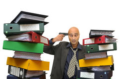 Desperate. Businessman with a gun and files everywhere isolated in white Stock Images