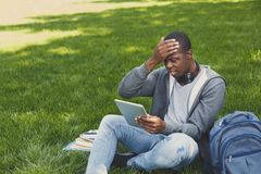 Desperate young man using tablet outdoors. Desperate african-american man using digital tablet outdoors. Unhappy student touching his head. Technology Royalty Free Stock Photography