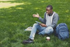 Desperate young man using tablet outdoors. Desperate african-american man using digital tablet outdoors. Unhappy student touching his head. Technology Stock Photography