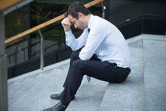 Desperate alone businessman after big fail sitting on the stairs stock images