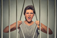 Desperate angry woman bending bars of her prison cell Stock Photos