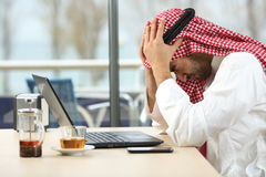 Desperate arab saudi man online bankruptcy. Profile of a desperate and alone arab saudi man with a laptop online in a coffee shop with a window in the background Stock Photos