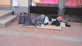 Free Desperate Beggar Man In Old Clothes Lying On Cardboard Box Stock Photography - 163323392