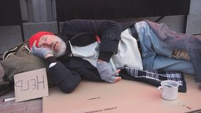 Desperate beggar man in old clothes lying on cardboard box