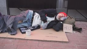 Desperate beggar man in old clothes lying on cardboard box asking for money, for any help.