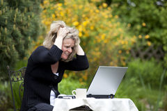 Desperate blond woman tearing her hair. A desperate beautiful mature blond woman sitting in her garden at her laptop and tearing her hair Royalty Free Stock Photo