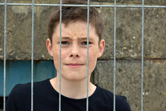 Desperate boy. Deaperate teenage boy behind the bars Royalty Free Stock Photography