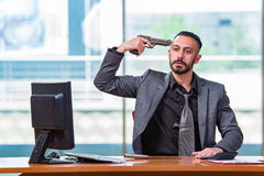 The desperate broke man committing suicide in the office Stock Image