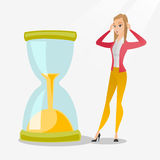 Desperate business woman looking at hourglass. Caucasian business woman looking at hourglass symbolizing deadline. Business woman worrying about deadline terms Stock Photography