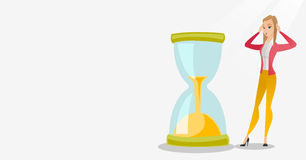 Desperate business woman looking at hourglass. Young business woman looking at hourglass symbolizing deadline. Business woman worrying about deadline terms Stock Image
