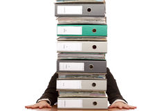 Desperate business woman sits behind folder stack Royalty Free Stock Photos