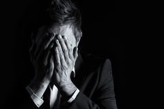 Desperate businessman covering his face. Low-key portrait of desperate office manager in dark suit covering his face with both hands, black & white conversion Stock Photography