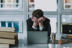 Desperate businessman hiding his face while sitting at workplace stock photography