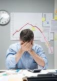 Desperate businessman with negative business chart. Desperate office worker with head in hands and negative financial chart on background Stock Photo