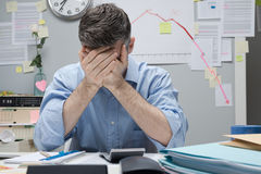 Desperate businessman with negative business chart. Desperate office worker with head in hands and negative financial chart on background Royalty Free Stock Image