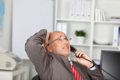 Desperate businessman using telephone Royalty Free Stock Image