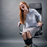 Desperate Businesswoman Shouting for Help. A desperate businesswoman tied up to an office chair screaming for help Stock Images