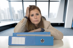 Desperate businesswoman suffering stress and headache at desk looking worried Stock Images