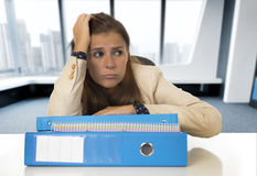 Desperate businesswoman suffering stress and headache at desk looking worried Royalty Free Stock Photography
