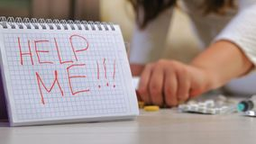Desperate child in depression. suicide. Depressive child sitting on the floor looking for hands with pills. Hands close up. In the foreground is a sign saying stock footage