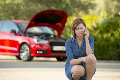 Desperate confused woman stranded with broken car engine crash accident calling on mobile phone. Young attractive desperate and confused woman stranded on Stock Image