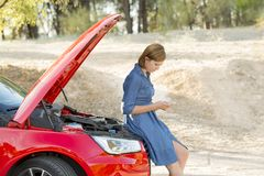 Desperate confused woman stranded with broken car engine crash accident calling on mobile phone Stock Images