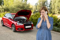 Desperate confused woman stranded with broken car engine crash accident calling on mobile phone Royalty Free Stock Photography