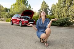 Desperate confused woman stranded with broken car engine crash accident calling on mobile phone Stock Photo