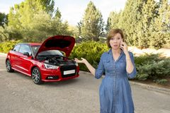Desperate confused woman stranded with broken car engine crash accident calling on mobile phone Stock Photography