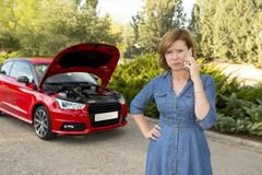 Desperate confused woman stranded with broken car engine crash accident calling on mobile phone Royalty Free Stock Images