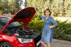 Desperate and confused woman stranded on roadside with broken car engine failure or crash accident Stock Photo