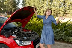 Desperate and confused woman stranded on roadside with broken car engine failure or crash accident. Young attractive desperate and confused woman stranded on Royalty Free Stock Image