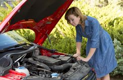 Desperate and confused woman stranded on roadside with broken car engine failure or crash accident Royalty Free Stock Image