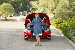 Desperate and confused woman stranded on roadside with broken car engine failure or crash accident Stock Images