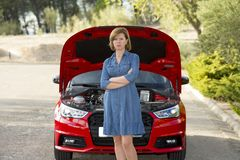 Desperate and confused woman stranded on roadside with broken car engine failure or crash accident Royalty Free Stock Photos