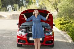 Desperate and confused woman stranded on roadside with broken car engine failure or crash accident Stock Photography