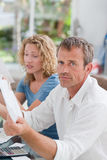 Desperate couple calculating their domestic bills Stock Photo