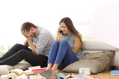 Desperate couple calling police after a robbery. Sitting on the floor of a messy living room at home Royalty Free Stock Photo