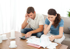 Desperate couple doing their accounts. Sitting on the sofa at home Royalty Free Stock Photo