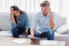 Desperate couple doing their accounts. In the living room stock photos