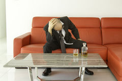 Desperate and depressed man with black suit spending time with bottle of whisky. Desperate man with black suit taking his head in his hands, depressed man Royalty Free Stock Images