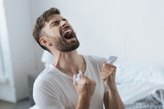 Desperate devastated man having a nervous breakdown. It is a failure. Desperate nice devastated man crying and holding pieces of crumbled paper while having a royalty free stock images