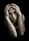 Desperate and fearful schizophrenic man. On black stock photography