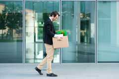 Desperate and fired businessman walking away from office. Sad fired businessman taking away his belongings from the financial district Royalty Free Stock Photos
