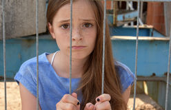 Desperate girl. Deaperate teenage girl  behind the bars Royalty Free Stock Photo