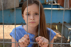 Desperate girl. Deaperate teenage girl  behind the bars Royalty Free Stock Images