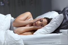 Desperate girl suffering insomnia trying to sleep stock photos